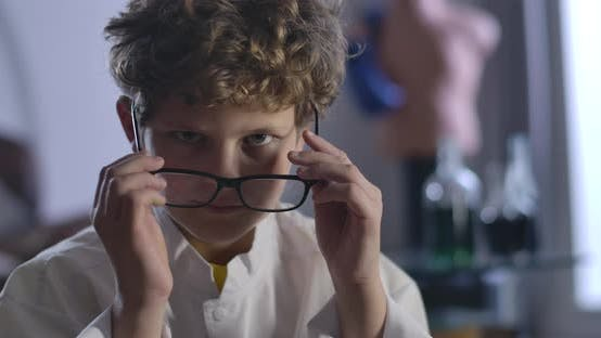 Thumbnail for Nahaufnahme von niedlichen kaukasischen Jungen mit lockigem Haar abnehmen und Brillen anziehen. Clever Teenager