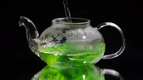 Thumbnail for Pouring Hot Water Into a Glass Teapot on a Black Background, Green Mint Tea