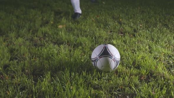 Football player kicks ball with run