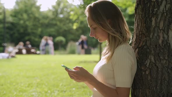 Thumbnail for Close Up of a Beautiful Young Woman, That Is Using an Application in Her Smart Phone in Park