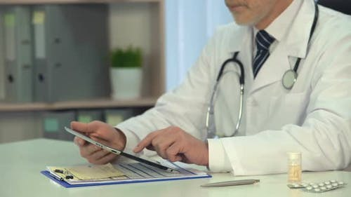 Male Physician Scrolling Information on Tablet, On-Line Consultation, Healthcare