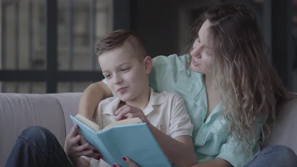 Cover Image for Portrait of a Beautiful Young Mother Reading a Book To Her Beautiful Son Sitting on the Sofa