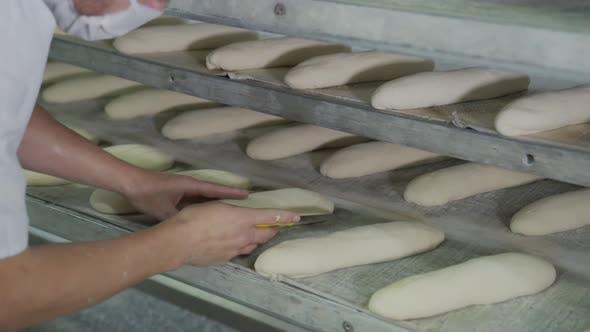 Bäckerei Backen Bäckerei, der Arbeiter macht Muster auf den Brötchen mit einem Backmesser