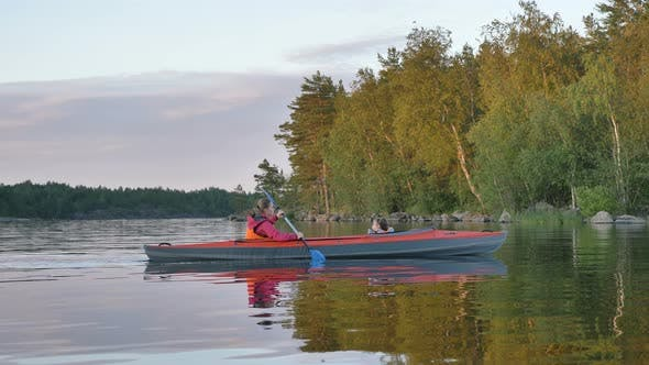 Thumbnail for Woman Rows Sports Kayak with Little Daughter Along Lake