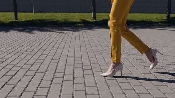 Female slim legs in high heels shoes walking in the urban street