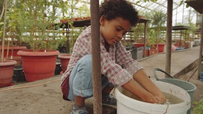 Afro-American Boy Washing Hands in Greenhouse