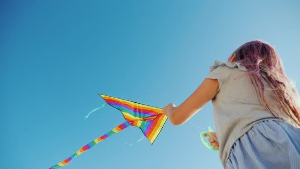 Cover Image for Low Angle Video - Girl Plays with Kite That Flies High in Blue Sky