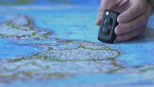Thumbnail for Toy auto stops near electronic car key on paper world map, transport for trips