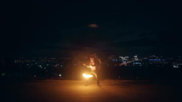Jeune homme blond fait la danse du feu avec deux torches, tourne des torches la nuit sur fond noir