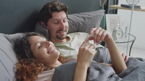 Romantic Couple Chatting in bed in Morning