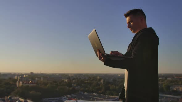 Thumbnail for Programmer a Hacker Is on the Roof with a Laptop at Sunset Says Error Code on the Keyboard and