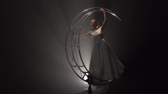 Thumbnail for Acrobat in the Costume of the Bride Performs Graceful Movements on a Rotating Design. Smoke