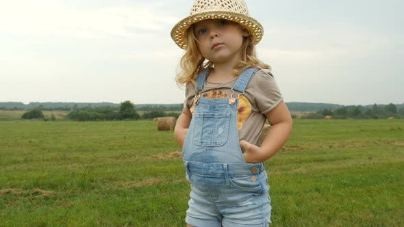 Thumbnail for Funny Child Standing on Haystack on Farmer Field. Farmer Daughter Walking in Field