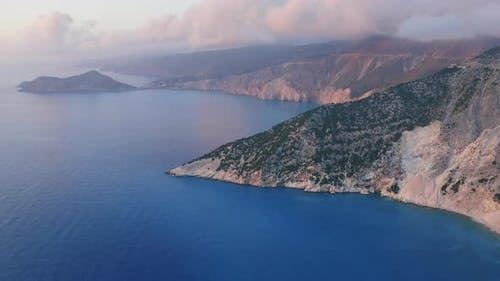 Aerial View of Kefalonia Coastline and Assos Village at Sunset Light and Low Clouds Moving