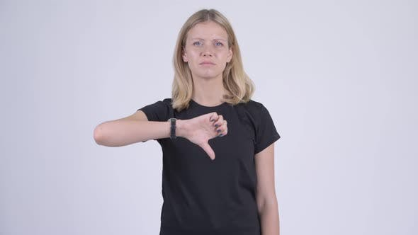 Cover Image for Young Sad Blonde Woman Giving Thumbs Down