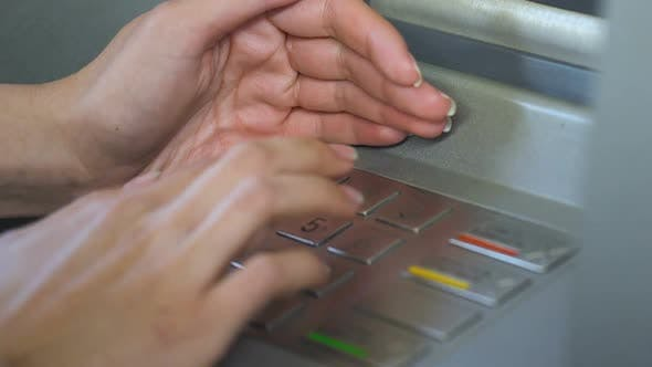 Female Entering Her Pin Code and Hiding Keyboard of Automated Teller Machine
