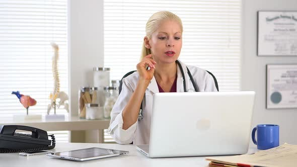 Thumbnail for Female doctor working on laptop computer