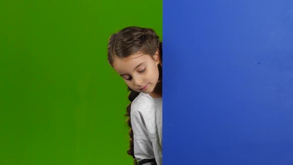 Thumbnail for Child Looks Out From Behind the Blue Board and Laughs. Green Screen