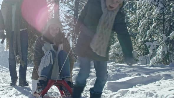 Cover Image for Boy Pulling Mother on Sled through Winter Forest