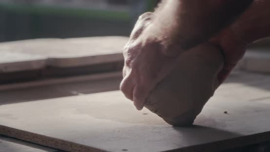 Crop Potter Kneading Clay on Workbench