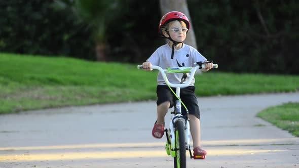 Thumbnail for A boy riding a bike in a park.