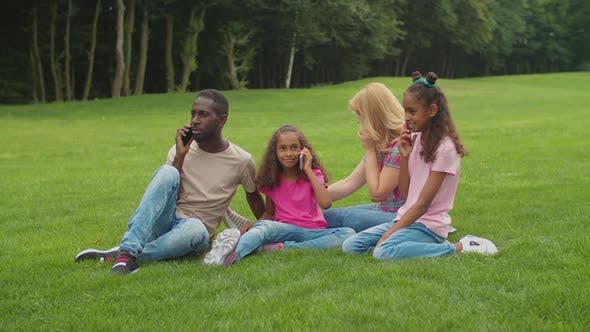 Thumbnail for Multiethnic Family Busy with Smart Phones Outdoors