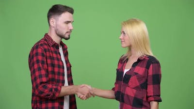 Young Couple Shaking Hands Together