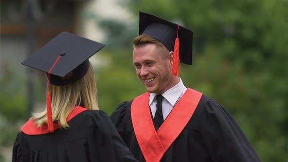 Thumbnail for Glückliche männliche und weibliche Absolventen feiern Abschluss, umarmt, glückliche Zukunft