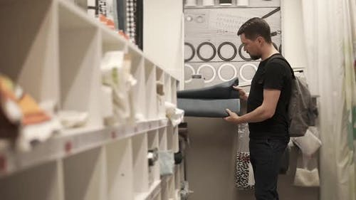Young Man is Examining Fabric in a Drapery Store Taking Rolls From Shelfs