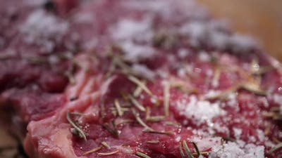 Salt Falling on Raw beef Steak with rosemary on board