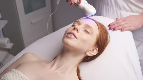 in a Modern Spa, a Cosmetologist Performs a Hardware Lift on a Woman's Face