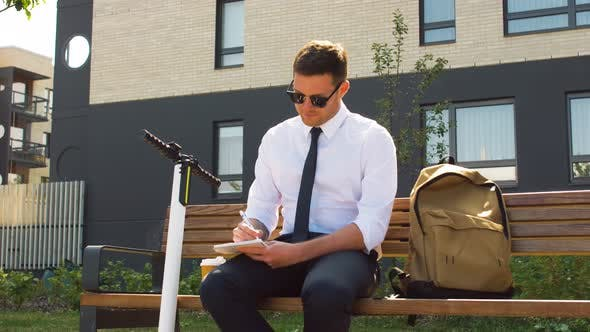 Thumbnail for Businessman Writing To Notebook Sitting on Bench