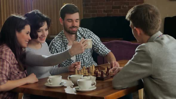 Thumbnail for Young Couple Playing Chess Indoor with Friends and Taking Selfie
