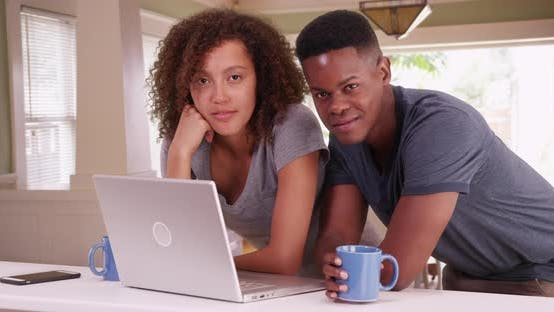 Thumbnail for African American man and woman use their laptop in their contemporary dining room