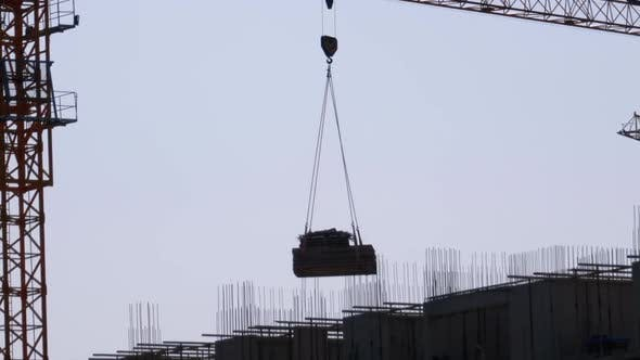 Thumbnail for Tower Crane on a Construction Site Lifts a Load at High-rise Building