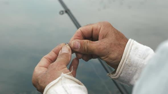 Fisherman preparing fishing gear for fishing. Man wrapping fishing line. Fishing on lake