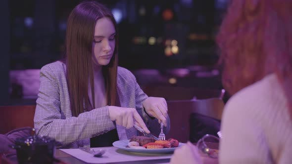 Thumbnail for Two Cute Girlfriends Eating in a Modern Restaurant Together. Girls Relax in the Restaurant and Enjoy