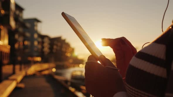 Cover Image for A Woman Uses a Smartphone in an Urban Setting at Sunset