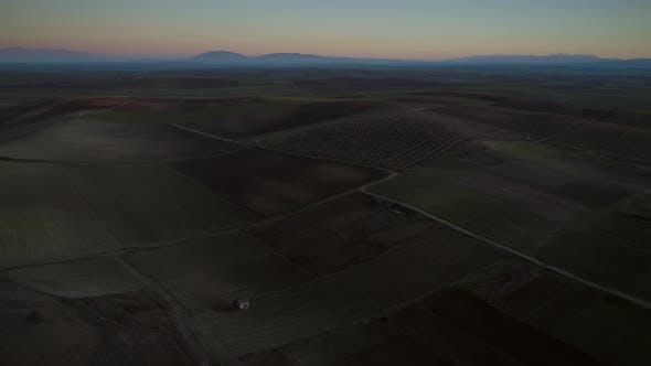 Thumbnail for Aerial view of a highway surrounded by agricultural fields at sundown.