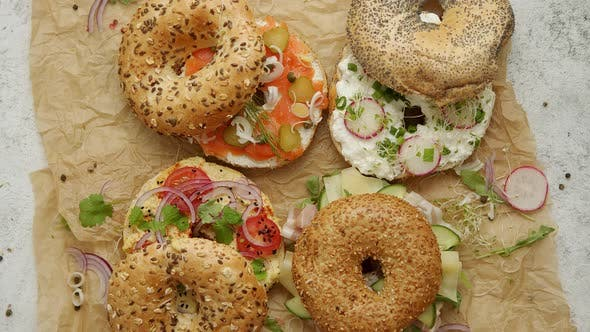 Leckere bunte verschiedene Bagels mit gesunden Zutaten serviert auf braunem Backpapier