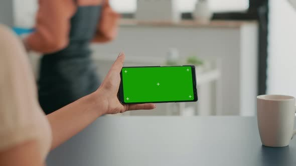 Freelancer Holding Smartphone with Mock Up Green Screen