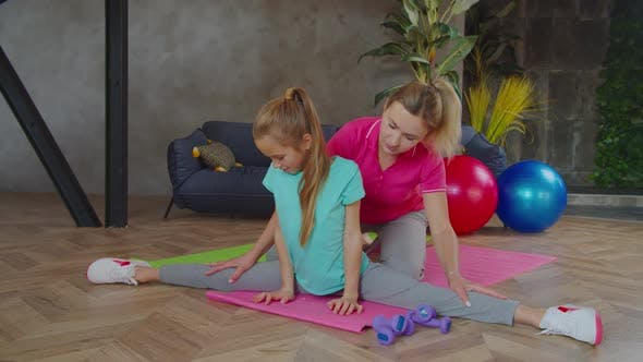 Caring Mother Helping Child Doing Side Splits Indoors