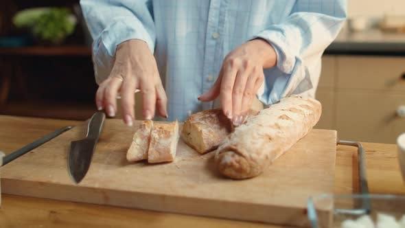 Thumbnail for Frau Hände schneiden Brot. Brünette weiblich Essen Baguette in Küche.