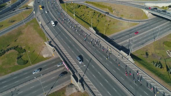 Aerial Drone Footage. Marathon Running Group on the Road Junction, Close Up Static Shot