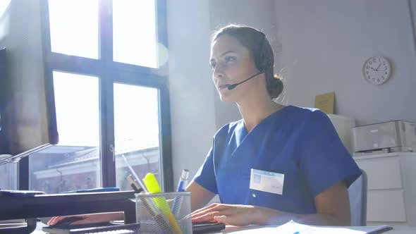 Doctor with Headset and Computer at Hospital