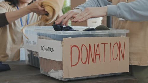 Putting Donated Items in Charity Boxes