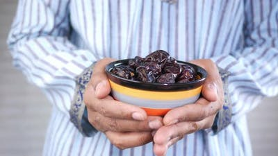 the Concept of Ramadan Hand Holding a Bowl of Date Fruits