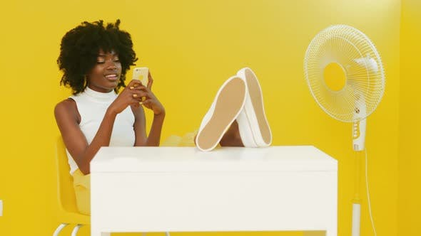 Thumbnail for Black Woman In Good Mood Is Using Mobile Phone