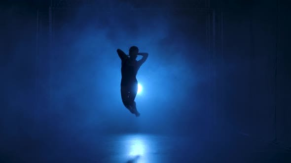 Silhouette a Professional Ballerina in Black Bodysuit Dancing Flexible in Darkness Under a