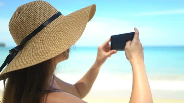 Thumbnail for Young Traveler Woman in Hat Taking Photo on Smartphone in Ocean Beach
